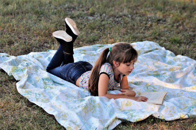 young-girl-reading-book-in-grass